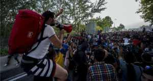 Egy migráns beszél hangosbeszélőn társa nyakában a Horgos-Röszke határátkelőhely magyar oldalán 2015. szeptember 16-án.  MTI Fotó: Sóki Tamás