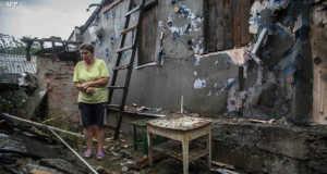 Egy ukrán asszony a háború által lerombolt házánál - AFP